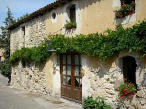 Fourcès - Facade of a house with wisteria and flowers