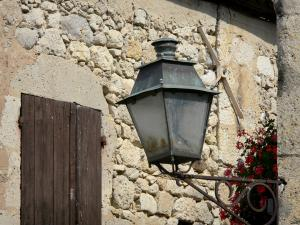 Fourcès - Wall lantern and stone facade of a house in the fortified village