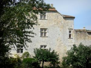 Fourcès - Facade of the castle pierced with mullioned windows, trees and foliage