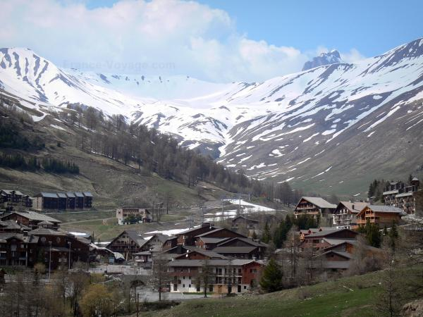 La Foux d'Allos - Chalets and buildings of the ski resort of Val d'Allos 1800, ski lifts and mountains with snowy tops