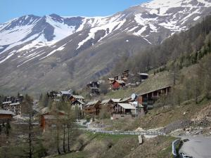La Foux d'Allos - Road, chalets of the ski resort of Val d'Allos 1800, trees and mountains with snowy tops