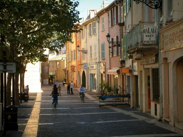 Fréjus - Trees on Formigé square, shops and houses with colourful facades in the old town