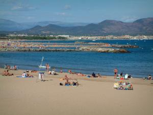 Fréjus - Fréjus-Plage: sandy beach with tourists, the Mediterranean Sea, cliffs, the Fréjus bay, and the hills in background