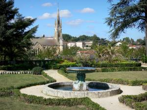 Fumel - Fountain of the French-style formal garden of the château with a view of the bell tower of the Saint-Antoine church