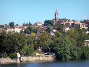 Fumel - Lot River, trees along the water, houses of the town and bell tower of the Saint-Antoine church overlooking the place