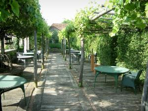 Gardens of the Notre-Dame d'Orsan priory - Pergola terrace with tables and chairs