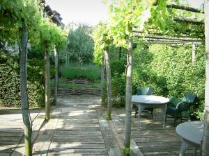 Gardens of the Notre-Dame d'Orsan priory - Tables and chairs on the pergola terrace, plants and trees in background