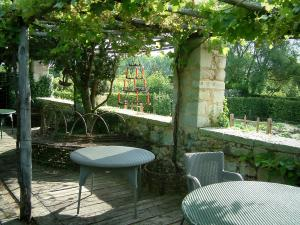 Gardens of the Notre-Dame d'Orsan priory - Tables and chairs on the pergola terrace, vegetable garden and trees in background