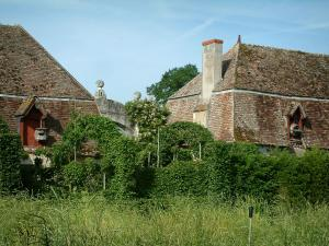 Gardens of the Notre-Dame d'Orsan priory - Buildings of the ancient monastery with plants and trees