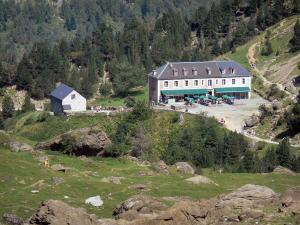 Gavarnie cirque - Cirque's hotel surrounded by trees, paths and rocks; in the Pyrenees National Park