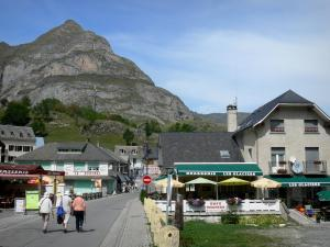 Gavarnie village - Street lined with houses and shops, mountain overhanging the set