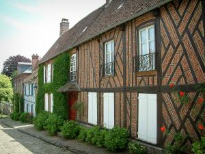 Gerberoy - Half-timbered house and bricks with white shutters, shrubs and a rosebush (red roses)