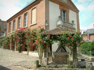 Gerberoy - Flower-bedecked well, brick-built house (town hall and museum) and climbing rosebushes (red roses)