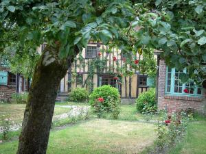 Gerberoy - Garden of a half-timbered house featuring a tree, rosebushes (red roses) and shrubs