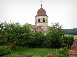 Gigny - Octagonal bell tower of the abbey church, flower-bedecked garden and trees