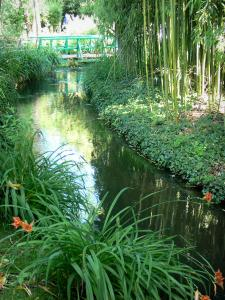 Giverny - Monet's garden: water gardin: river Ru, orange lilies, bamboo, and small green bridge in the background