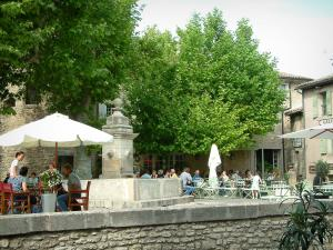 Gordes - Square in the village with a fountain, cafe terraces and trees