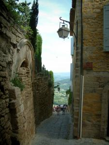 Gordes - Sloping narrow street, houses and hills far off