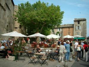 Gordes - Square in the village with café terraces, parasols, trees and houses