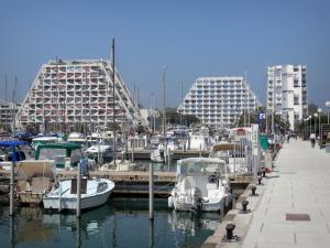 La Grande-Motte - Seaside resort: pyramid-shaped buildings, boats and sailboats of the sailing port and the quay