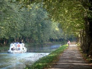 Greenway of the Garonne canal - Bicycle lane of the Voie Verte greenway with cyclists, plane trees (trees), and boat sailing on the Garonne canal; in Damazan