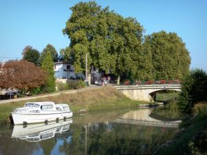 Greenway of the Garonne canal - Garonne canal, moored boats, flower-bedecked bridge and trees; in Buzet-sur-Baïse