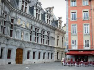 Grenoble - Facade of the former Palace of the Dauphiné Parliament (former courthouse) of Renaissance style, colorful facade of a house and café terrace on the Place Saint-André square