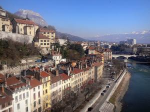 Grenoble - Facades of houses and buildings of the town, quays, River Isère and mountains in the background