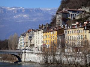 Grenoble - Facades of houses in the town, bridge spanning River Isère, trees and mountains
