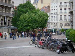 Grenoble - Line of bikes, trees, tram, shops and facades of the town