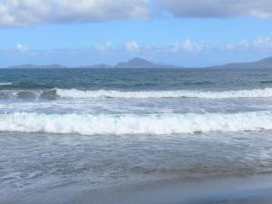 Guadeloupe beaches - Grande Anse beach on the island of Basse-Terre, in the town of Trois-Rivieres: view of Les Saintes islands and the waves of the sea from the Grand Anse beach