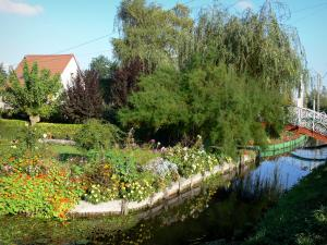 Hortillonnages of Amiens gardens - Flower garden decorated with trees and flowers along the water and small bridge spanning the canal