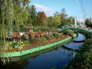 Hortillonnages of Amiens gardens - Flower garden along the water, small bridge spanning the canal, trees