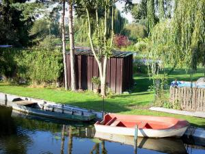 Hortillonnages of Amiens gardens - Garden with small house and trees on the edge of the canal, boats on the water