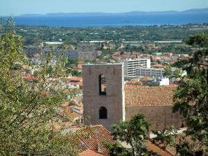Hyères - View of trees, the Romanesque bell tower of the Saint Paul collegiate church, roofs of houses and buildings of the city, coasts and the Mediterranean Sea in background
