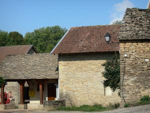 L'Isle Crémieu plateau - Facades of stone houses and roofs with slate and terra cotta tiles of a village