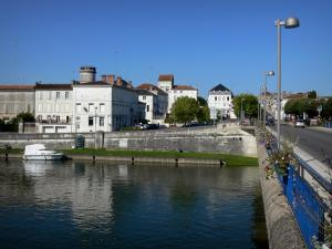 Jarnac - Bridge featuring lampposts, Charente river, boat on the water and houses of the city