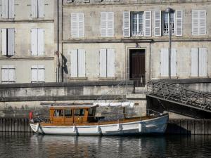 Jarnac - Wooden boat moored to the quay, Charente river and facades of houses