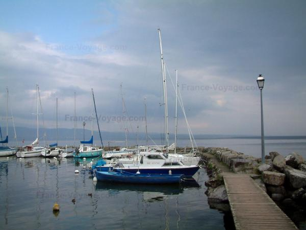 Lake Geneva - Sailboats  of the fishermen port in Yvoire, lamppost, pier, lake and Swiss shore in background