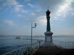 Lake Geneva - Évian-les-Bains shore, lighthouse, lamppost, lake with a boat, Swiss shore and clouds in the sky
