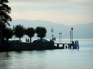 Lake Geneva - Lake, Meillerie shore with trees, flags and lampposts in the shadow, mountains in background