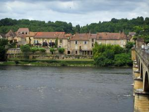 Lalinde - Houses of the fortified town, trees and bridge spanning the River Dordogne, cloudy sky, in the Dordogne valley