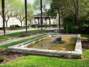 Lamalou-les-Bains - Square of the spa town with a fountain, benches, trees and bandstand