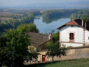 Landscapes of the Ain - Houses of the town of Trevoux overlooking River Saône lined by trees (Saône valley)