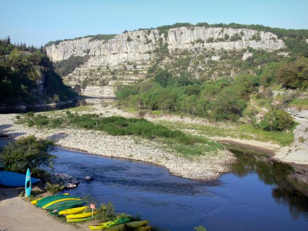 Landscapes of the Ardèche - Ardèche valley, in Balazuc: canoes laid along River Ardèche; cliffs overlooking the place