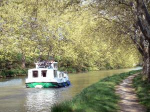 Landscapes of the Aude - Canal du Midi: towpath shaded by plane trees and ship sailing on the waterway