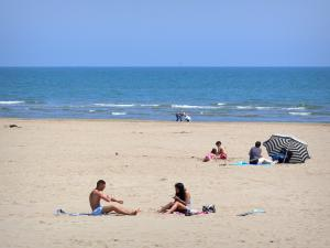 Landscapes of the Aude - Gruissan-Plage, in the Regional Natural Park of Narbonne in the Mediterranean: holidaymakers on the sandy beach, at the edge of the Mediterranean sea