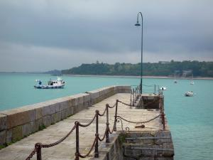 Landscapes of the Brittany coast - Cancale: pier decorated with a lamppost, boats on the sea, coast and turbulent sky