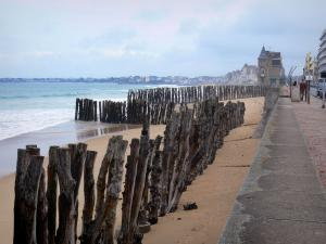 Landscapes of the Brittany coast - Emerald Coast: beach with wooden pickets, walk, building and houses alongside the beach and the sea, in Saint-Malo