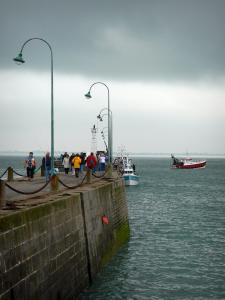 Landscapes of the Brittany coast - Cancale: pier decorated with lampposts, fishing boats on the sea and turbulent sky